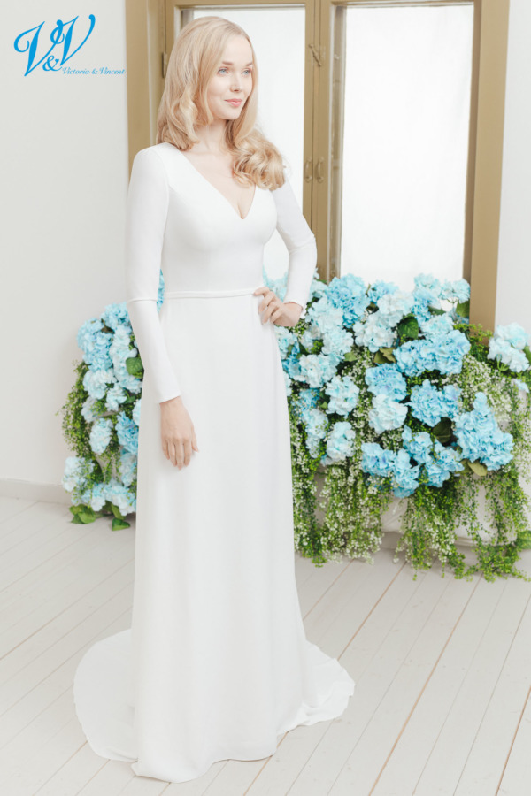 Simple ivory bridal dress with sleeves. With a closed back and made from high-quality crepe. Color in the picture is ivory but this bridal gown is also available in white.