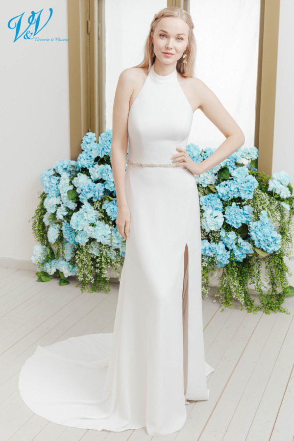 Halter-neck wedding dress for an elegant look. This plain wedding gown has a slit skirt and is made from crepe. Color in the picture is ivory but this bridal gown is also available in white.