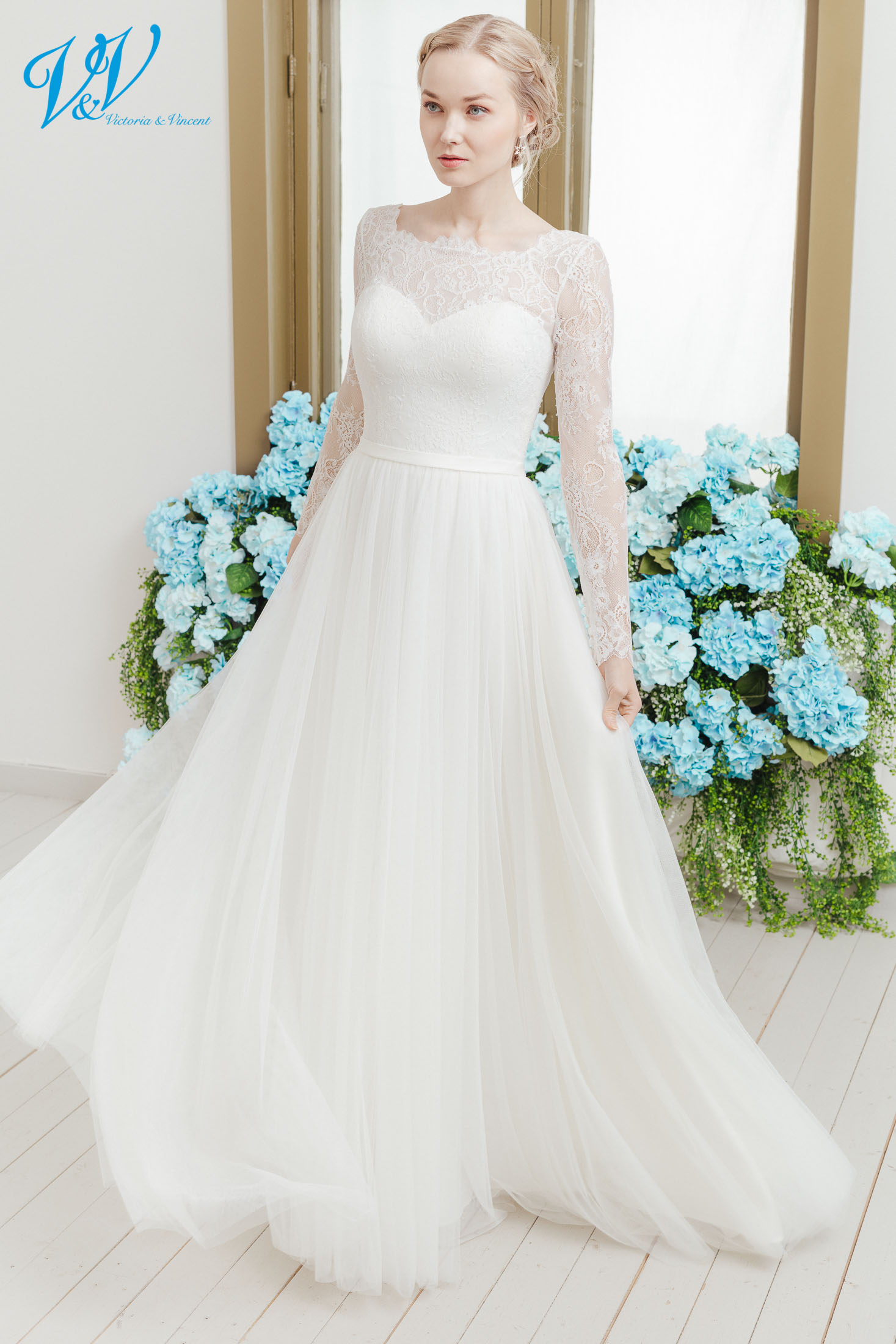 Traditional wedding dress with long sleeves, a high neckline and a soft tulle skirt. This classy bridal gown is perfect for a church wedding. Color in the picture is ivory but this bridal gown is also available in white.