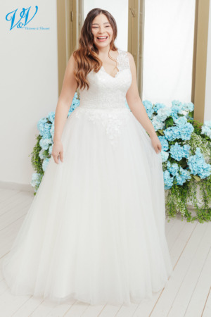 Romantic plus size wedding dress that makes you feel like a princess on your big day. Wide shoulder straps and V-neckline for a classic look. Built-in corset belt for additional support. Color in the picture is ivory but this bridal gown is also available in white.