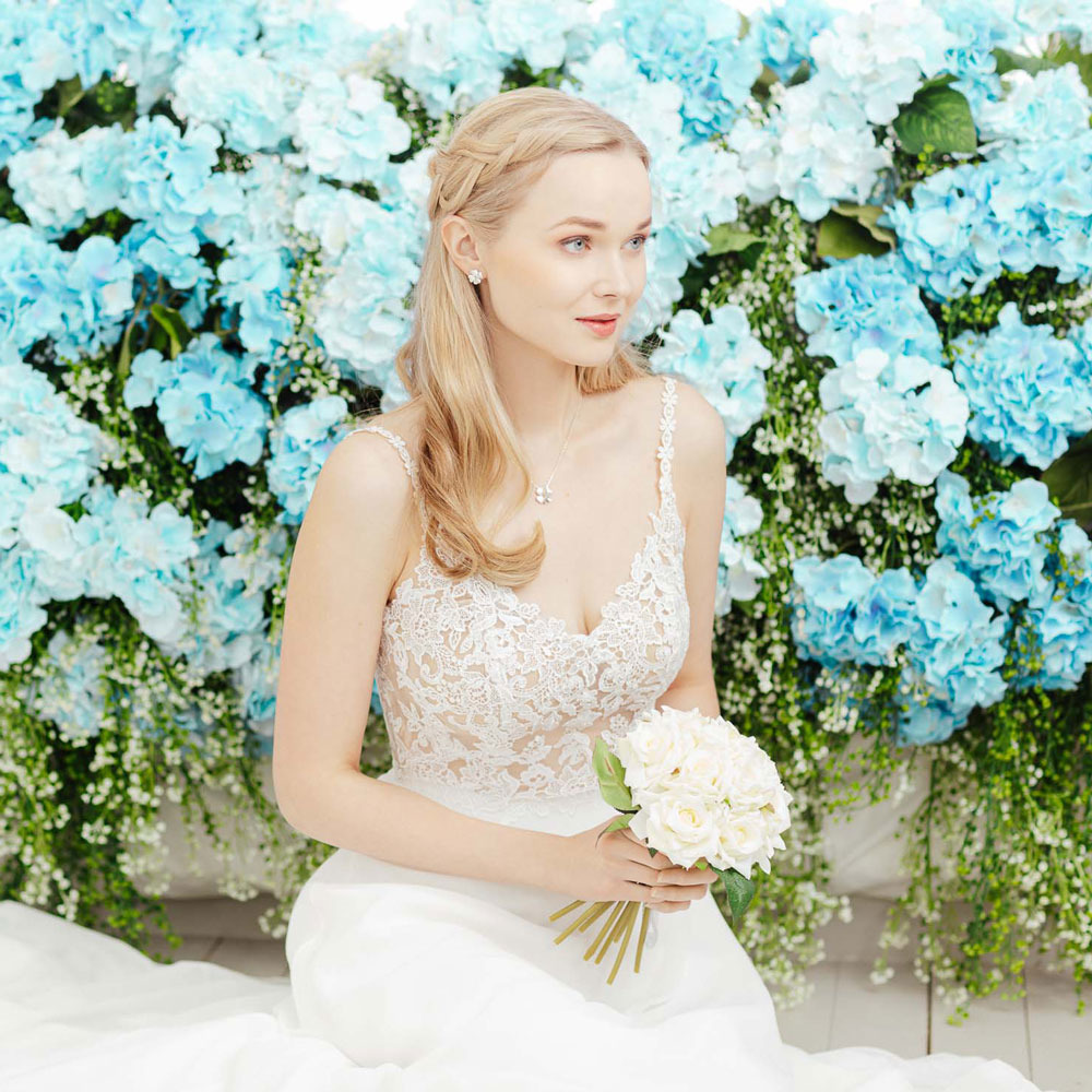 Affordable ivory color lace wedding dress from Victoria & Vincent. Bride in front of wall of flowers.